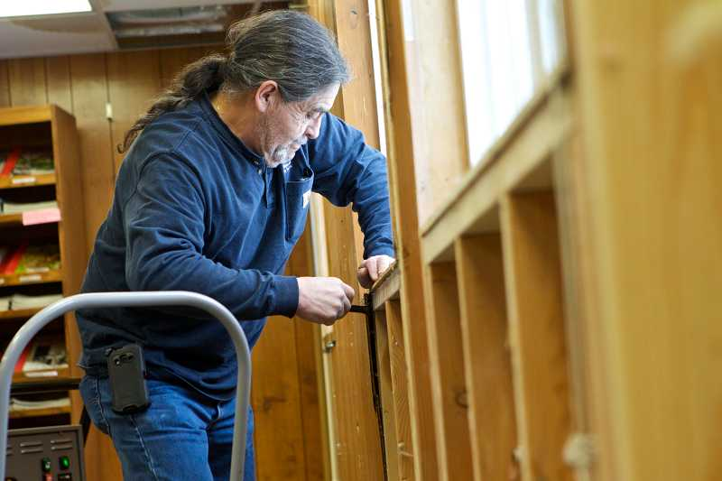 by: TIMES PHOTO: JAIME VALDEZ - Gary Casaus, an environmental technician with the Washington County Facilities Department, removes wood paneling from a wall in the West Slope Community Library.
