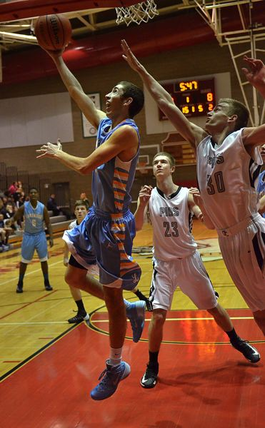 by: VERN UYETAKE - Lakeridge's Max Minervini attempts a reverse lay-up in the Pacers' road in over Oregon City Tuesday.