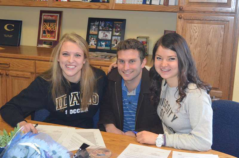 by: JEFF GOODMAN / PAMPLIN MEDIA GROUP - Longtime friends Olivia Baggerly (left) and Chloe Bell (right), shown with Canby girls soccer coach Ben Winegar, sign letters of intent Feb. 5 at Canby High School to continue their athletic careers at Idaho.