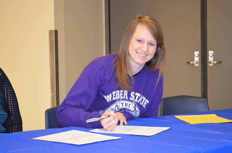 by: JEFF GOODMAN / PAMPLIN MEDIA GROUP - Wilsonville javelin thrower Rebecca Wenz signs a letter of intent Feb. 5 to continue her athletic career at Weber State.