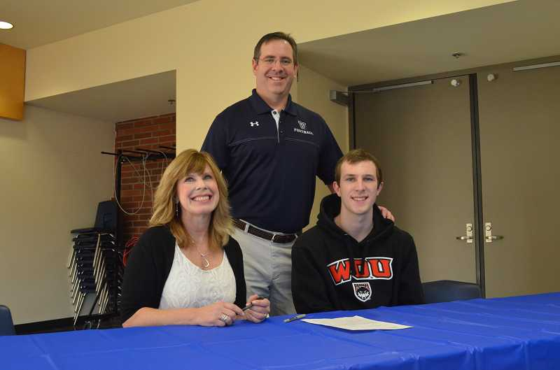 by: JEFF GOODMAN / PAMPLIN MEDIA GROUP - Derek Sunkle (right), who will continue his football career at Western Oregon, signs a letter of intent Feb. 5 at Wilsonville High School. He is joined by his mother, Judy, and Wildcats coach Adam Guenther.