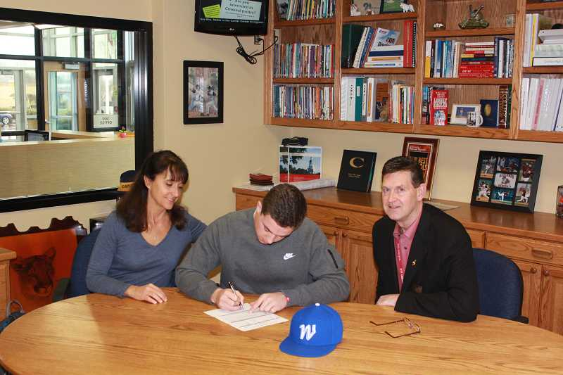 by: J.J. STOLSIG / COURTESY - Canby senior Parker Woodley (center), flanked by his parents, Lynn and Tim, signs a letter of intent Feb. 11 to continue his baseball career at Western Nevada College.