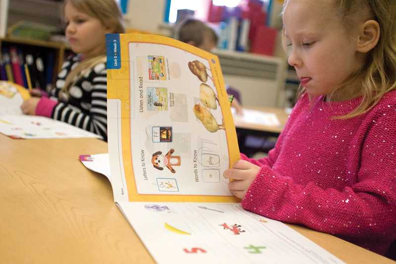by: KEVIN SPERL - Rylee Donnelly works in her reading curriculum activity book in Karen Bryant's kindergarten class at Crooked River Elementary.