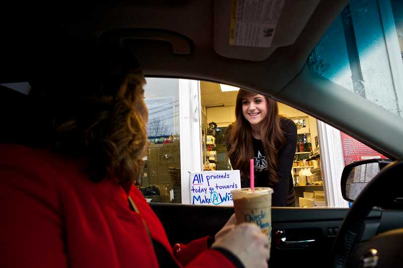 by: TIMES PHOTO: JAIME VALDEZ - Customer Teresa Fear catches up with Dutch Bros. Manager Kristin Motsinger after several days without coffee because of the snowy weather. Beaverton Dutch Bros. is donating all the proceeds from Tuesday to the Make-A-Wish Foundation of Oregon.
