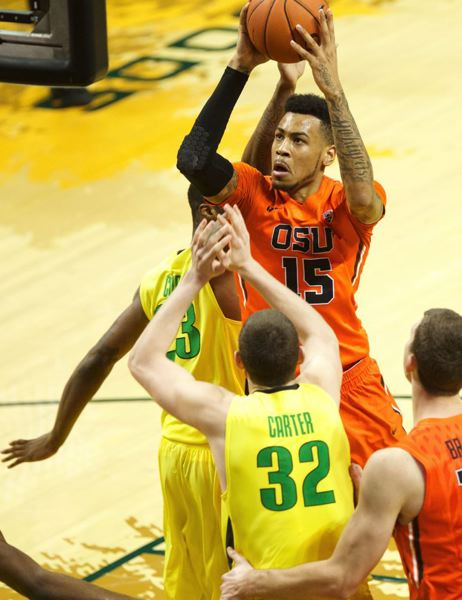 Beavers forward Eric Moreland takes a shot over Ducks forwards Ben Carter and Elgin Cook.