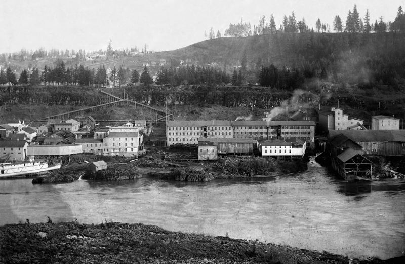 by: CLACKAMAS COUNTY HISTORICAL SOCIETY - In this 1892 photograph, a waterwheel housing can be seen jutting into 3rd Street (center) and the water discharge from the Brick Mill flume (left) can be seen cascading down the tailrace into the Willamette River.