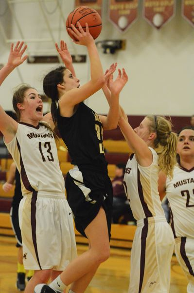 by: JOHN WILLIAM HOWARD - Freshman Maggie Cochran shoots over the Milwaukie defense during the Lions' 63-33 loss on Tuesday evening. Cochran is part of a young group of players that hopes to do big things in the coming years.