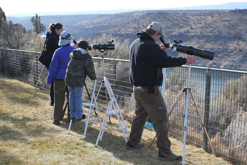 by: HOLLY M. GILL - Viewers use spotting scopes to locate eagles on cliffs and overhangs above Lake Billy Chinook at the 2013 Eagle Watch.