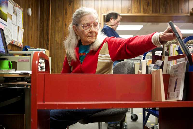 by: TIMES PHOTO: JAIME VALDEZ - Dee Buffum, who has been a volunteer at the West Slope Community Library for 30 years, checks in books to be placed back on the bookshelves of the community library.