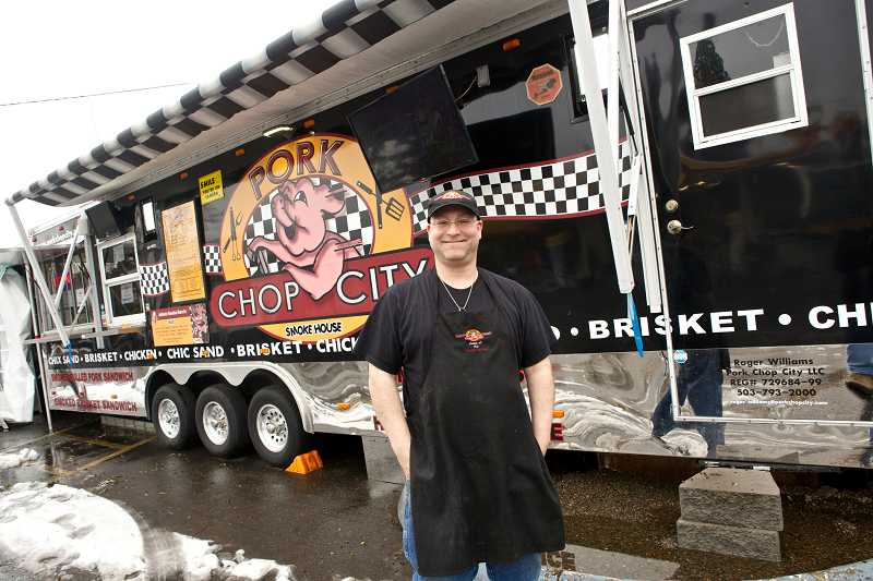 by: TIMES PHOTO: JAIME VALDEZ - Troy Herren, manager and chef at Pork Chop City Smoke House, shows off the whimsically decorated barbecue truck now stationed across from Jesuit High School on Beaverton-Hillsdale Highway.