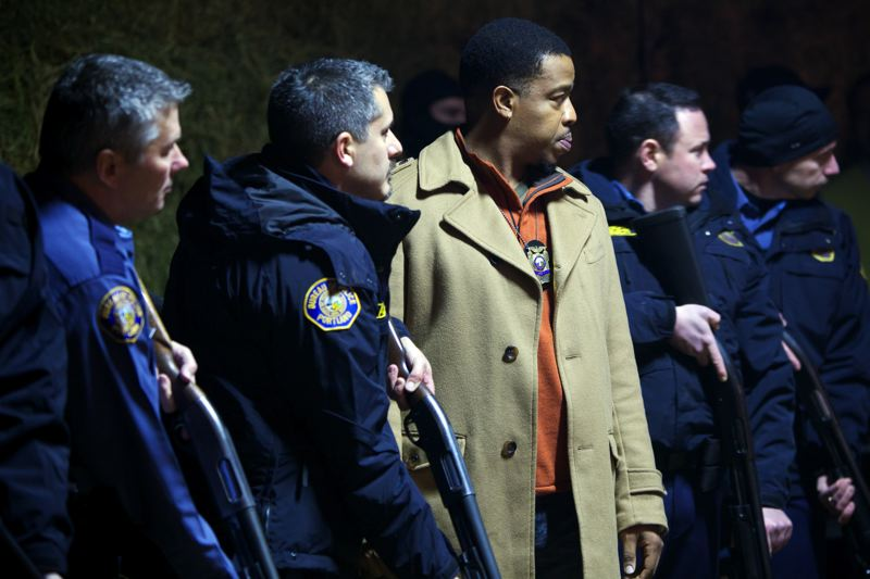 by: COURTESY OF NBCUNIVERSAL - When Grimm needs extras in police uniforms it uses real Portland officers. Here, left to right, Det. Mike Perry, officer Steve Johns, actor Russell Hornsby, Det. Ken Reynolds and Det. Darren Posey prepare for action.