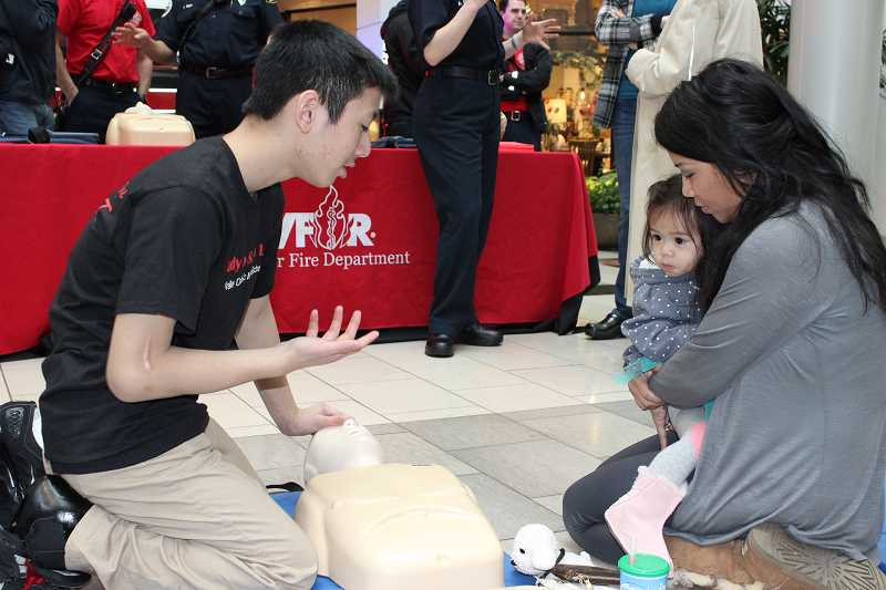 by: SUBMITTED PHOTO - An Luu, 14, expalins the basics of hands-only CPR at Washington Square on Saturday. All Valley Catholic Middle School students learn CPR and then teach the skill to members of the community
