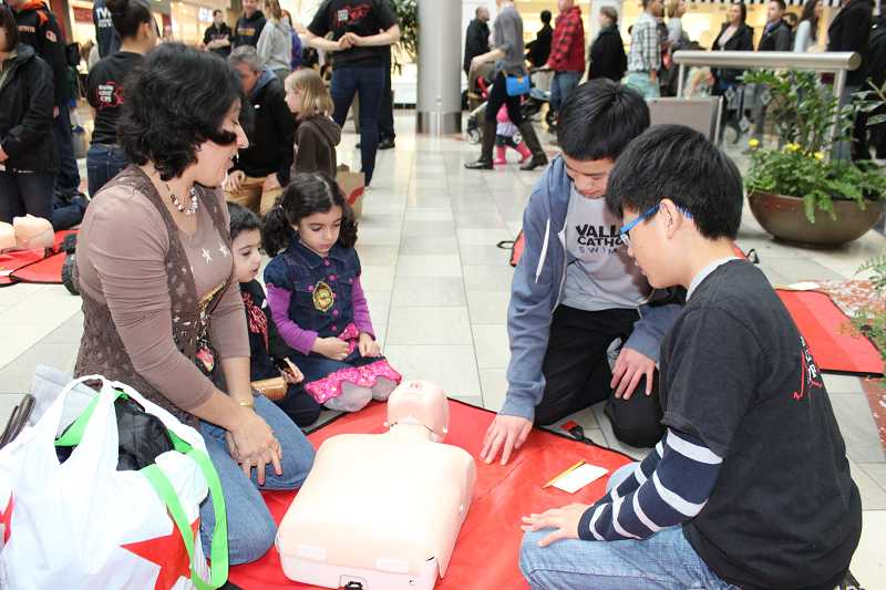 by: SUBMITTED PHOTO - Valley Catholic Middle School students Joshua Cheng and Brandon Jeong teach a family the basics in hands-only CPR at Washington Square mall on Saturday.
