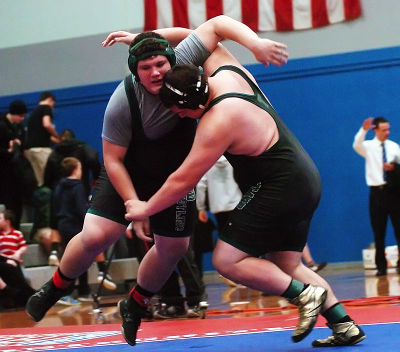 by: DAN BROOD - TIGER TUSSLE -- Tigard seniors Victor Ceja (right) and Justin Jackson do battle in the 285-pound match Saturday during the finals of the Special District 3 regional tournament, held at McNary High School.
