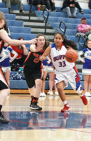 by: BILLY GATES/THE PIONEER - Madras guard Leah Suppah drives to the bucket during the White Buffalos' 60-40 win against Molalla.