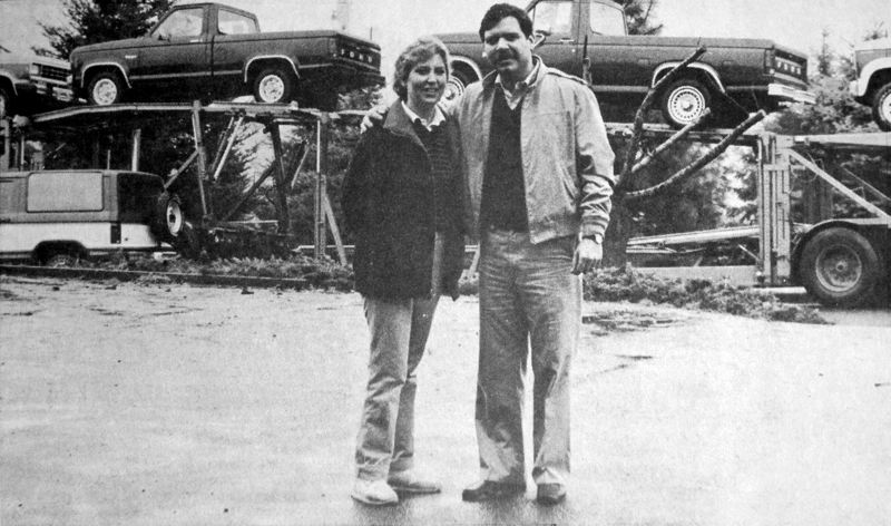 by: CONTRIBUTED PHOTO - Nancy Jaksich (left) and husband Jerry posed in front of their first delivery of Ford vehicles in 1984. The couple opened the dealership on Highway 26 and Ten Eyck Road, using a trailer as a sales office.