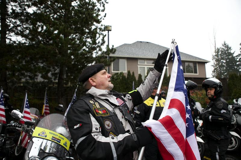 by: TIMES PHOTO: JAIME VALDEZ - Patriot Guard Rider and veteran Harold 'Butch' Scott unrolls an American flag before joining other veterans lining the entrance to the funeral service for 2010 Sunset High School graduate Spc. John A. Pelham.