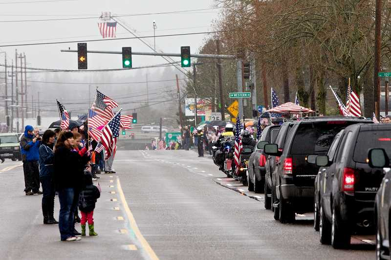 by: TIMES PHOTO: JAIME VALDEZ - Community members lined Southwest Beaverton-Hillsdale Highway on Monday afternoon to show their respect to U.S. Army Spc. John Pelham and his family.