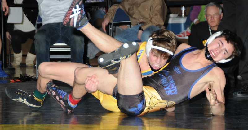 by: LON AUSTIN/CENTRAL OREGONIAN - Trayton Libolt attempts to turn teammate Johnny Avina onto his back in the championship round of the 113-pound weight class. Libolt went on to win the match 4-0. The Cowboys easily defended their district championship with 10 wrestlers earning district titles and six more finishing in second.