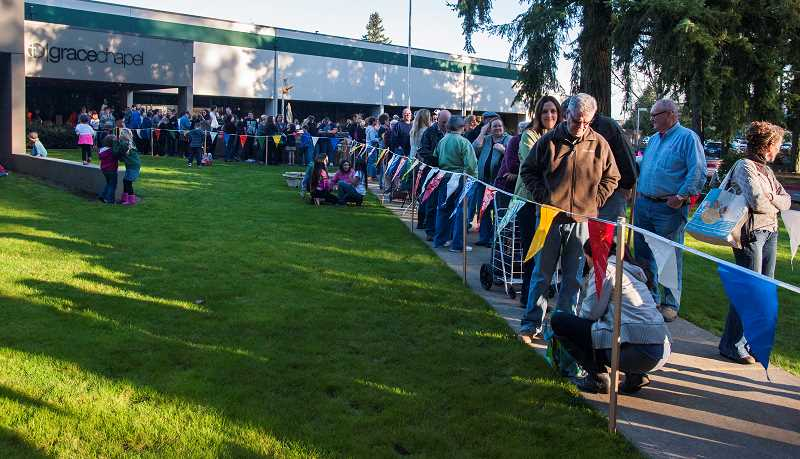 by: SPOKESMAN FILE PHOTO: JOSH KULLA - The lines always stretch across the parking lot at the start of the annual Grace Chapel rummage sale. So come early to this year's sale, set to kick off at 5 p.m. March 7.
