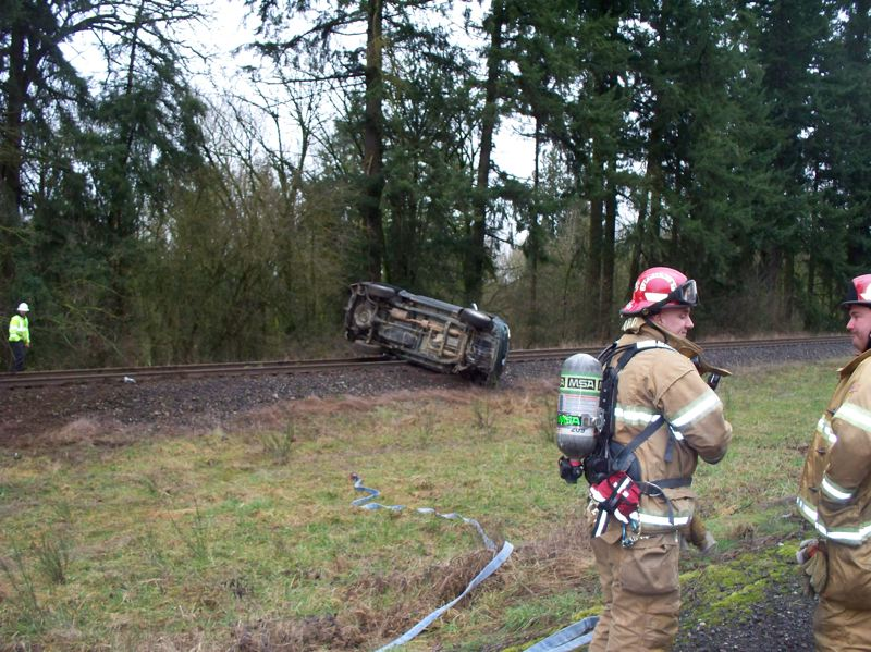 Photo Credit: COLUMBIA RIVER FIRE & RESCUE COURTESY PHOTO - Firefighters respond to the scene of a wreck on Highway 30 Monday, Feb. 24, in Deer Island. A Toyota Tundra pickup truck, one of two vehicles involved in the crash, rolled over and came to a stop on the railroad tracks alongside the highway.