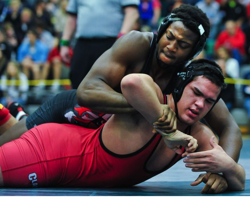 by: JOHN LARIVIERE - Clackamas junior Kyle Anderegg (bottom) had a tough time fighting off David Douglas standout Osawaru Odighizuwa at last weekends regional championship wrestling tournament. Odighizuwa beat Anderegg 7-2 in the 220-pound final and remained undefeated on the season with the win.
