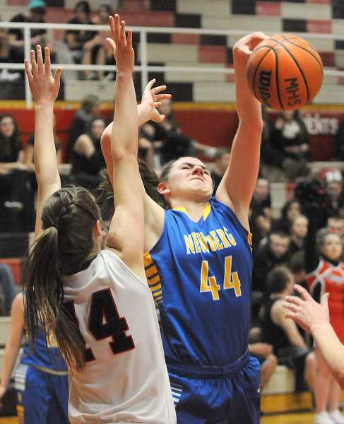 by: SETH GORDON - Tough boards - Junior center Tori Eicthen loses control of the ball during Newberg's 55-41 loss to McMinnville Friday night. Eichten led the Tigers with 14 points and nine rebounds.
