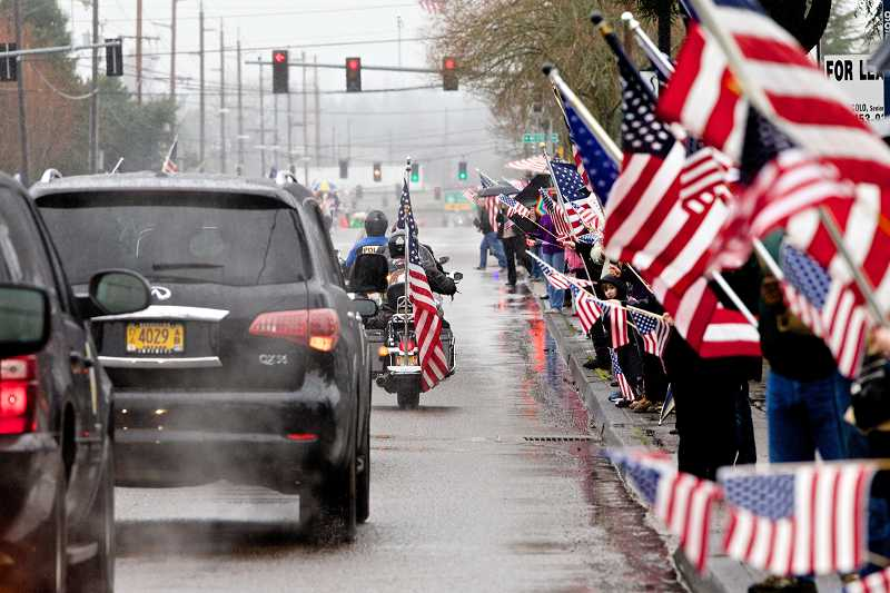 by: PAMPLIN MEDIA GROUP PHOTO: JAIME VALDEZ - Hundreds of people line up Monday along Beaverton-Hillsdale Highway and show their respects as the funeral procession for U.S. Army Spc. John Pelham passes by.