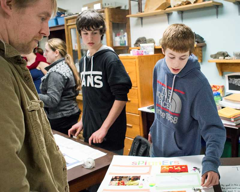 by: NEWS TIMES PHOTO: CHASE ALLGOOD - Alec Lecarno shows Adam Norman his capstone project on creating fishing lures.