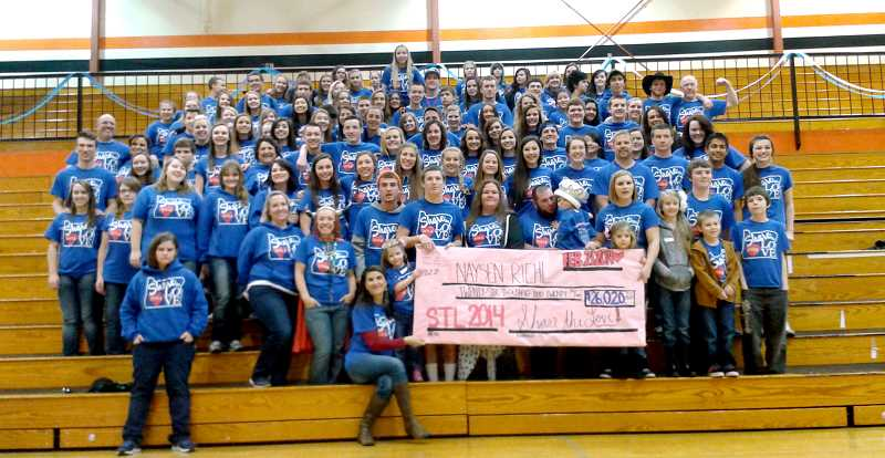 by: CORY MIMMS - MHS students presented a check for $26,020.20 to the Riehl family on Friday, Feb. 21, during the Share the Love closing assembly.