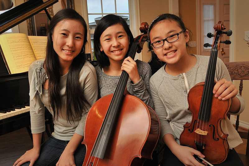 by: REVIEW, TIDINGS PHOTO: VERN UYETAKE - The Yoon Trio always makes happy music together. Especially in the living room of their home. From the left are Lauren, Taylor and Ashley.