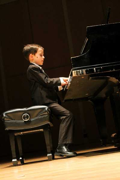 by: NEWS-TIMES PHOTO: JOHN SCHRAG - Caleb Richardson, 7, plays 'The Happy Farmer' on the piano from memory and draws a strong audience response.