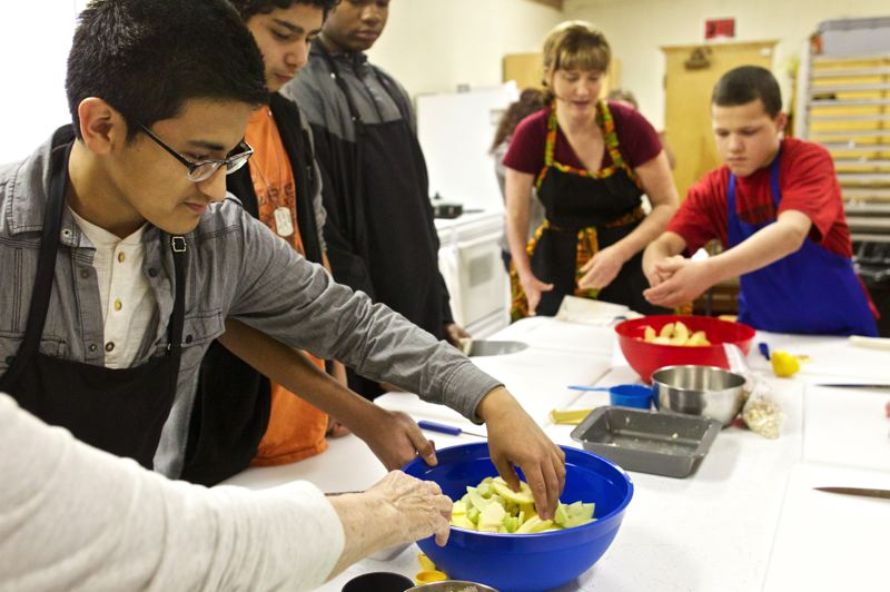 by: TRIBUNE PHOTO: JAIME VALDEZ - Delfino Gurrola,16, mixes ingredients for an apple crisp during a cooking class last week at St. Michaels Lutheran Church.