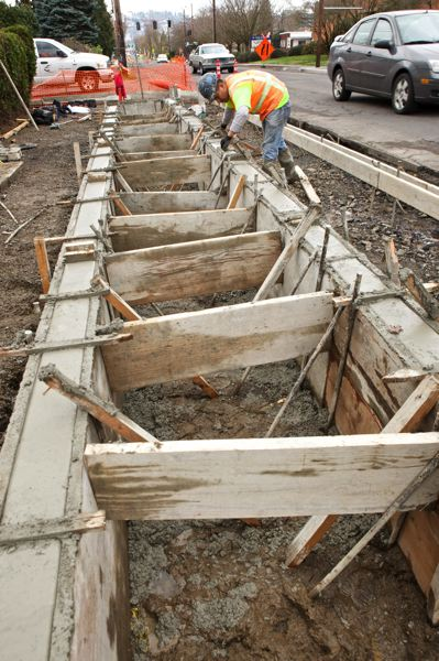 by: TRIBUNE PHOTO: JAIME VALDEZ - Apareceo Lopez levels concrete at a new bioswale under construction along Southeast Division Street.