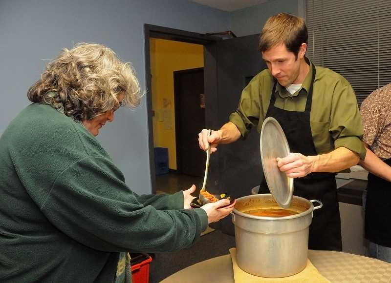 by: REVIEW PHOTO: VERN UYETAKE - Teacher Greg Mylet served Barbara Huis seconds at the Lake Oswego Junior High Empty Bowls fundraiser during Fine Arts Night on Feb. 20.