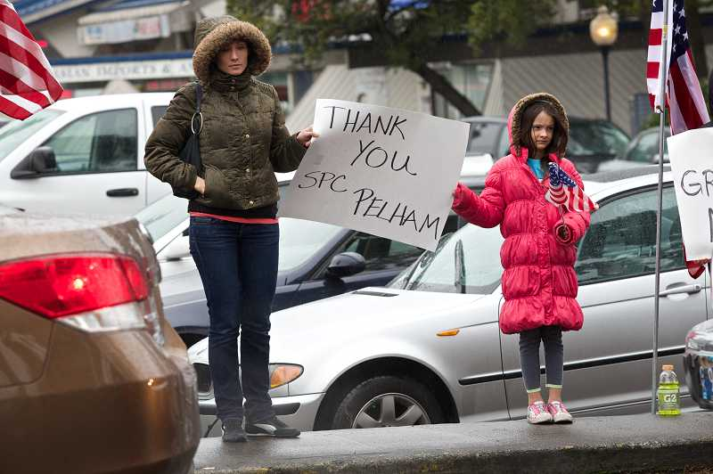 by: TIMES PHOTO: JAIME VALDEZ - Tanya Thompson of Lake Oswego and her daughter, Jane, 9, hold a sign for U.S. Army Spc. John Alexander Pelham before a funeral procession at the corner of 99th Avenue and Beaverton-Hillsdale Highway.
