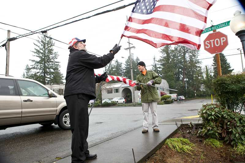by: TIMES PHOTO: JAIME VALDEZ - Sam Corey of Bethany, left, helps Scott Thompson of Lake Oswego place American flags along Beaverton-Hillsdale Highway in front of the McCormick & Schmick's restaurant for the funeral procession of U.S. Army Spc. John A. Pelham. Thompson read Pelham's story in the newspaper and wanted to help support the family by placing American flags along the procession route.