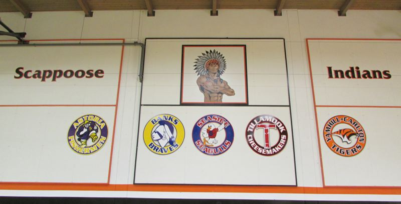 by: FILE PHOTO - The Scappoose Indians name and symbol on the wall of the Scappoose High School gymnasium. The emblem of the Banks Braves, of Banks High School, is among the other team logos on the wall.