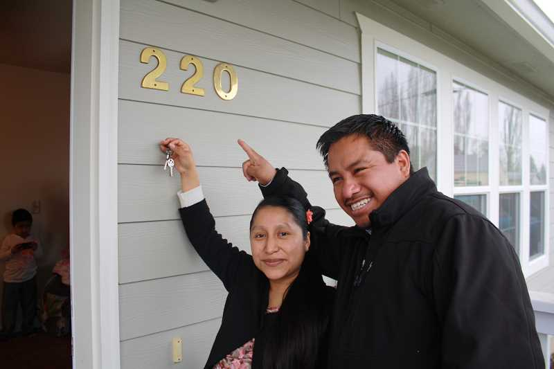 by: BETH FAULHABER - Antonia Cruz and her husband Gerardo Goveche celebrate receiving the keys to their new home in Gervais.
