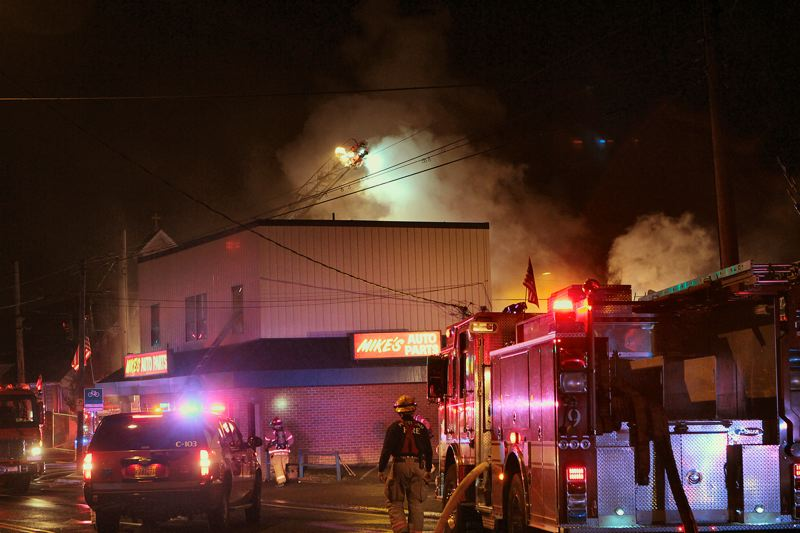 by: DAVID F. ASHTON - An aerial ladder illuminates the roof at Mikes Auto Parts during this major fire in Woodstock.
