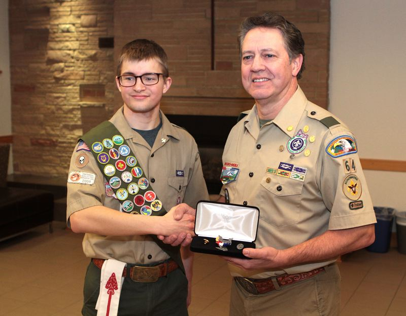 by: DAVID F. ASHTON - At his Eagle Scout Investiture Ceremony, David Mair is congratulated by Eagle Mentor of Boy Scout Troop 64, Jim Sharp.