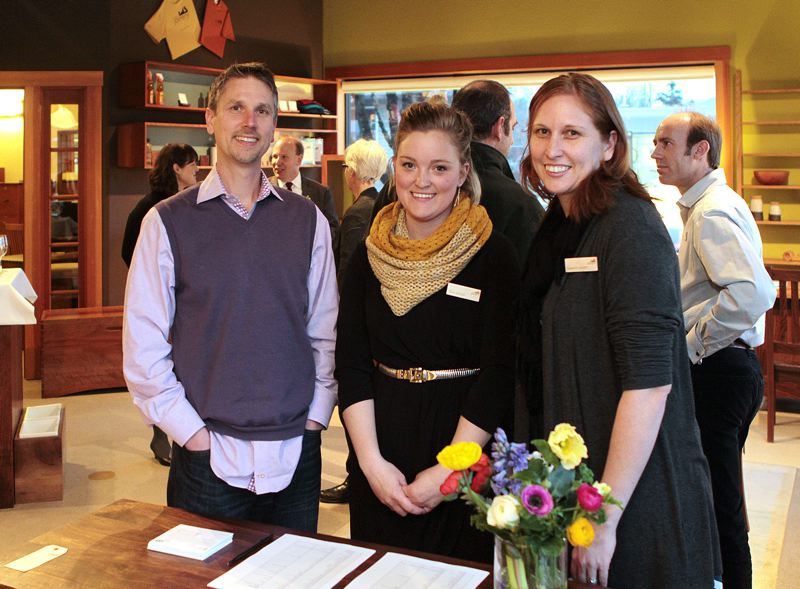 by: DAVID F. ASHTON - The new owner of The Joinery, Jon Blumenauer, stands with staff members Taryn Johnson and Cassandra Jackson, to welcome guests to a recent reception at the Woodstock business.