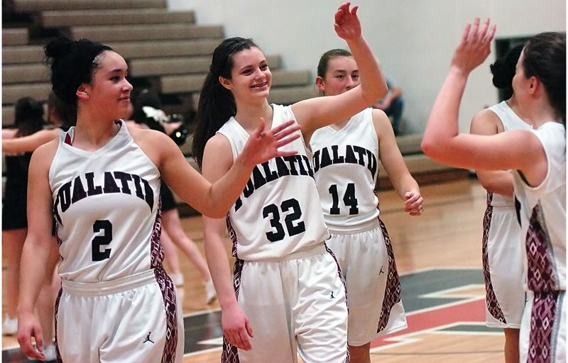 by: DAN BROOD - GOOD JOB -- Members of the Tualatin High School girls basketball team, including senior Jasmine Miller (2), senior Savannah Heugly (32) and sophomore Emily Leonard (14) congratulate each other following the Wolves state playoff win over Centennial.
