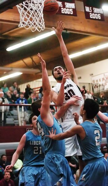 by: DAN BROOD - ABOVE AND BEYOND -- Sherwood High School senior post Jordan Kurahara goes up high to shoot over three Liberty defenders during Friday's NWOC finale. The Bowmen won 50-25 to clinch the conference title.