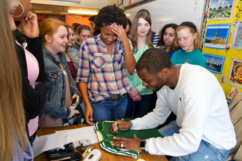 by: SUBMITTED PHOTO: TOM BERRIDGE - Frederic Piquionne autographs a Timbers' jersey for OES soccer standout Mikaela McKinney Griggs.