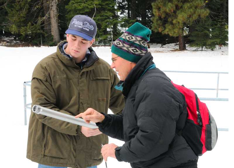 by: LON AUSTIN - Clark Woodward (LEFT) and instructor Rick Kramer look at a core sample of snow taken from the Ochoco Meadows SNOTEL site.  The CTE Natural Resource Management Program at Crook County High School accompanied Ochoco Irrigation District manager Mike Kasberger to the site Tuesday morning to check snow depths.