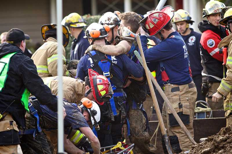 by: TIMES PHOTO: JAIME VALDEZ - Tualatin Valley Fire & Rescue firefighters carry Danny Russu, 21, an Apollo Excavation employee, toward an ambulance after rescuing him from a sewer line trench.