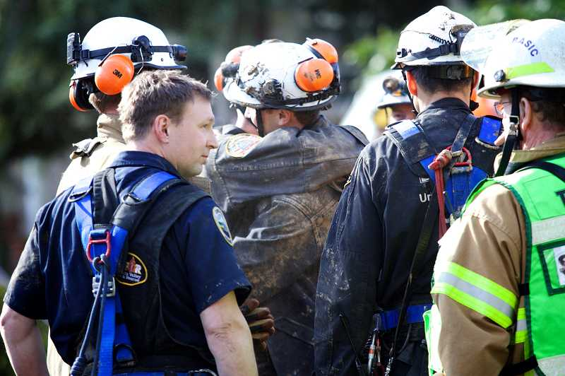 by: TIMES PHOTO: JAIME VALDEZ - Tualatin Valley Fire & Rescue firefighters Kyle Leonard and Donavan Rodriguez embrace after helping in the successful effort to rescue trapped excavation worker Danny Russu from a 12-foot deep trench.