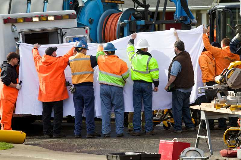 by: TIMES PHOTO: JAIME VALDEZ - Workers hold up a sheet to block the view of Apollo Excavation worker Danny Russu as crews place him in an ambulance. Crews rescued him from a trench on Monday.