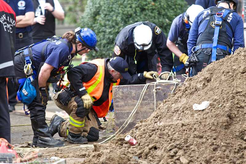 by: TIMES PHOTO: JAIME VALDEZ - Emergency personnel from Tualatin Valley Fire & Rescue and Portland Fire & Rescue monitor the condition of a man trapped in a trench 12 feet below the surface.